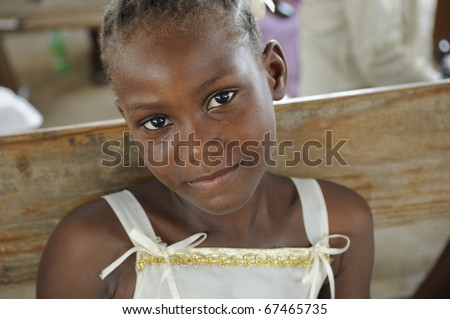 PORT-AU-PRINCE - AUGUST 22: An unidentified Haitian child sharing a smile during a food distribution camp,in Port-Au-Prince, Haiti on August 22, 2010. - stock photo