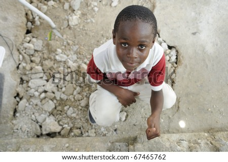 """PORT-AU-PRINCE - AUGUST 22: An unidentified Haitian kid shows a """"thumb up"""" sign during a food distribution camp in Port-Au-Prince, Haiti on August 22, 2010. - stock photo"""