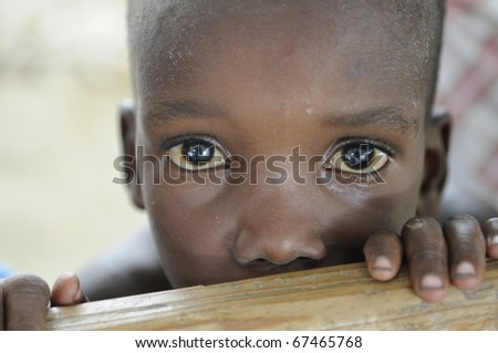 PORT-AU-PRINCE - AUGUST 22: An unidentified poor Haitian kid looking with surprise towards the photographer during a food camp ,in Port-Au-Prince, Haiti on August 22, 2010. - stock photo