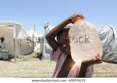 PORT-AU-PRINCE - AUGUST 28: An unidentified young boy carrying a bottle of water after the water arrived in the tent city ,in  Port-Au-Prince, Haiti on August 28, 2010. - stock photo