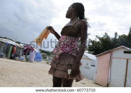 PORT-AU-PRINCE - AUGUST 28: An young woman waiving her handkerchief in on of the Tent cities  on August 28, 2010 in Port-Au-Prince, Haiti - stock photo