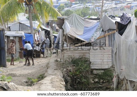 PORT-AU-PRINCE - AUGUST 28: Children and the adults passing their time by playing cards or  outdoor games in on of the Tent City on August 28, 2010 in Port-Au-Prince, Haiti - stock photo