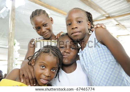 PORT-AU-PRINCE - AUGUST 22: Four unidentified Haitian kids having fun amongst themselves during a food distribution camp,in Port-Au-Prince, Haiti on August 22, 2010.