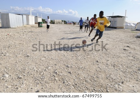PORT-AU-PRINCE - AUGUST 30:  Haitian teenagers playing soccer in the tent camps , a favorite sport of the Haitians,  in Port-Au-Prince, Haiti on August 30, 2010. - stock photo