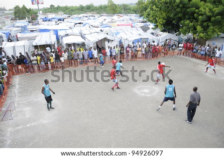 PORT-AU-PRINCE - AUGUST 26: Resident enjoying one of their primary form of entertainment- a soccer game in one of the tent cities  in Port-Au-Prince, Haiti on August 26, 2010. - stock photo