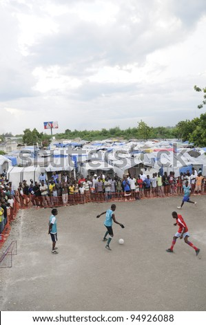 PORT-AU-PRINCE -AUGUST 26: Residents gathered around a small soccer playground within a tent city to witness a friendly soccer game between two tent cities in Port-Au-Prince,Haiti on August 26, 2010. - stock photo