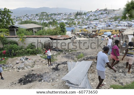 PORT-AU-PRINCE - AUGUST 28:  Residents gathering their belongings after their tents was destroyed due to fire, on August 28, 2010 in Port-Au-Prince, Haiti - stock photo