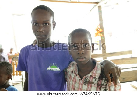 PORT-AU-PRINCE - AUGUST 22: Two young unidentified Haitian adults posing for the camera during a food distribution camp in Port-Au-Prince, Haiti on August 22, 2010. - stock photo