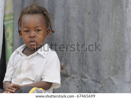 PORT-AU-PRINCE - SEPTEMBER 2: An unidentified Haitian Child  sitting on the doorstep of her tent , in Port-Au-Prince, Haiti on September 2, 2010. - stock photo