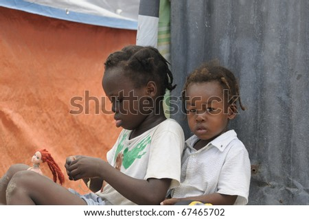 PORT-AU-PRINCE - SEPTEMBER 2: An unidentified Haitian girl playing with her doll and another one  keeps looking towards the photographer, in Port-Au-Prince, Haiti on September 2, 2010. - stock photo
