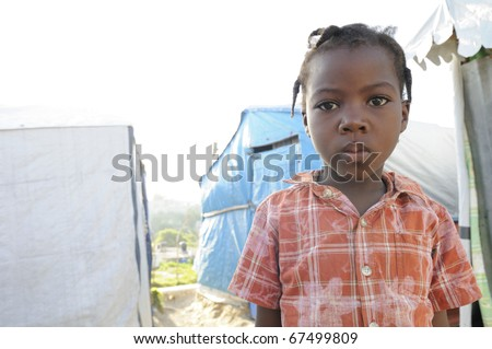 PORT-AU-PRINCE - SEPTEMBER 2:   An unidentified Haitian kid  posing for the camera  on the walkway of her tent city,in Port-Au-Prince, Haiti on September 2, 2010. - stock photo