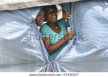 PORT-AU-PRINCE - SEPTEMBER 1:Camp residents peeping out through their tent window to watch a rally passing,  in Port-Au-Prince, Haiti on September 1, 2010. - stock photo