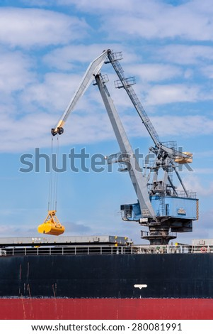 Port crane in Gdansk, Poland, with the closed grabbing bucket loading / unloading the ship - stock photo