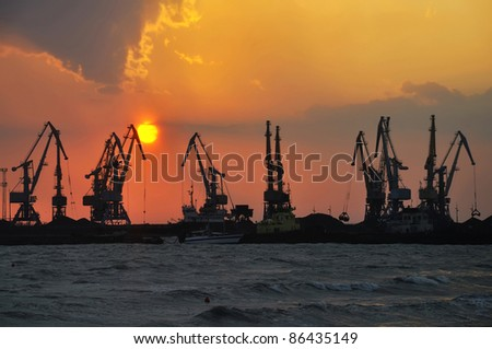 Port cranes at sea at the setting sun (at the end of the day)