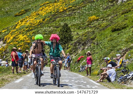 PORT DE PAILHERES,FRANCE- JUL 6: Two young men funny disguised climbing the  road to the Col de Pailheres before the race during the stage 8 of edition 100 of Le Tour de France on July 6 2013. - stock photo