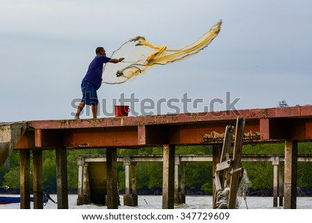 PORT DICKSON, MALAYSIA - 5 DECEMBER 2015 : Man throwing fishing net from the bridge