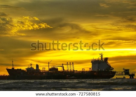 PORT DICKSON, MALAYSIA 01 OCTOBER 2017 : Silhouette. Selective focus. Sunset at the beach with Cargo Ship and beautiful yellow sky.