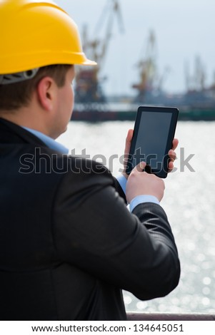 Port engineer is using the digital tablet - stock photo