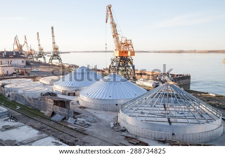 Port equipped with cranes, silos, warehouses and railways - stock photo