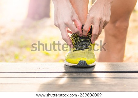 port, fitness, exercise and lifestyle concept - runner man lacing trainers shoes - stock photo