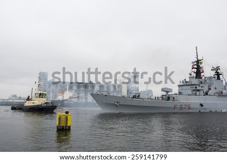 Port of Amsterdam, Noord-Holland/Netherlands - March 09-03-15 -  Italian Navy Warship F575 leaving the shore. Tugboat Zeeland connected at the Warship for Towing service. Smoke from engine. - stock photo