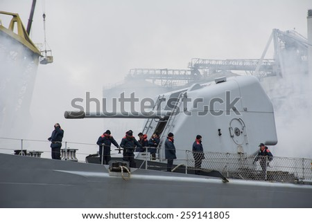 Port of Amsterdam, Noord-Holland/Netherlands - March 09-03-15 -  Italian Navy Warship F575 leaving the shore. Sailors from the navy standing next to the Cannon of warship F575. Smoke from engine. - stock photo