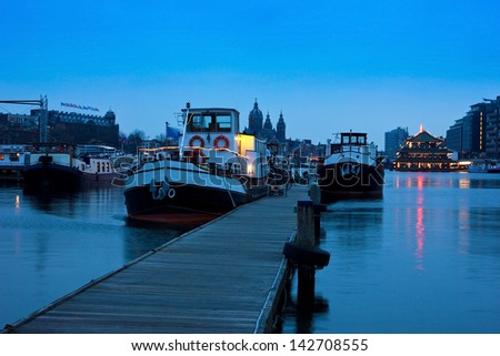 Port of Amsterdam oosterdok before dawn with The Church of St Nicholas at the background. - stock photo