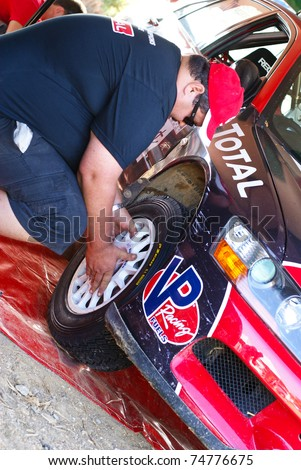 PORT OF SPAIN- APRIL 3: Mechanic works on a car during the Trinidad and Tobago 2011 Motor Car Rally meet April 3, 2011 in Cipero, Trinidad & Tobago. - stock photo
