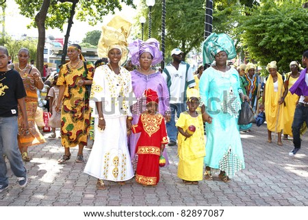 PORT OF SPAIN - AUGUST 1: unidentified kids and family celebrating Emancipation Day which commemorates the abolition of Slavery August 1, 2011 in Port Of Spain, Trinidad & Tobago. Colorful & elaborate headpieces are usually worn. - stock photo