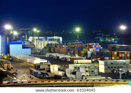 Port warehouse with cargoes and containers at night - stock photo