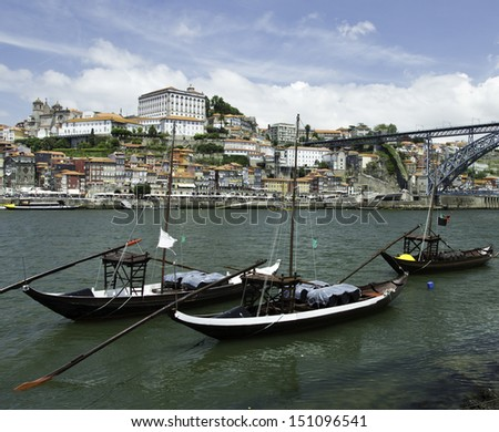 Port wine boats on Douro River with Porto Portugal in background - stock photo