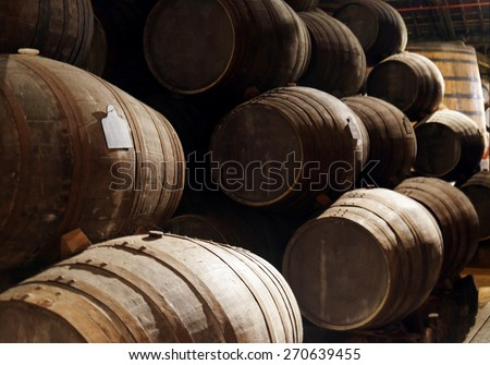 Port wine from the vineyards Douro Valley in Portugal aging in oak barrels stacked in the old traditional dark cellar. Product of organic farming. - stock photo