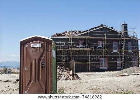 Porta Potty sits near a new house under construction. - stock photo