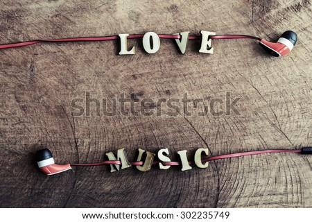 "portable audio earphones on old wood textured with word ""Love music"" - stock photo"
