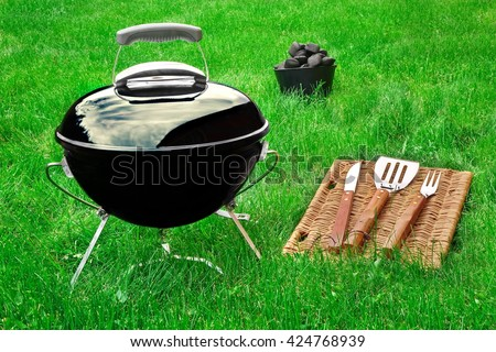 Portable Barbecue Grill ,  Charcoal Briquettes And BBQ Tool On The Fresh Backyard Grass, Summer Picnic Or Party Or Cookout Concept - stock photo