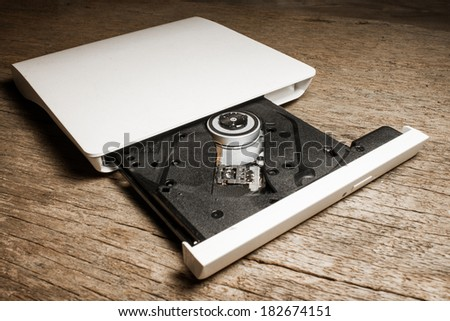 Portable Cd / Dvd external drive on wooden background  - stock photo
