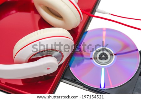 Portable computer with DVD compact disc and red white headphones isolated - stock photo