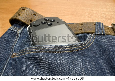 portable electronic game player in the pocket of a demin jeans - stock photo