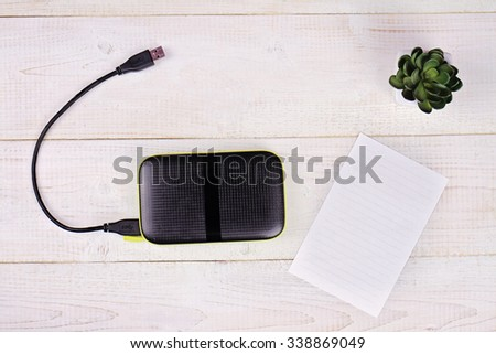 Portable external hard disk drive with USB cable  and blank message paper on white wooden background  Copy space image, flat lay - stock photo