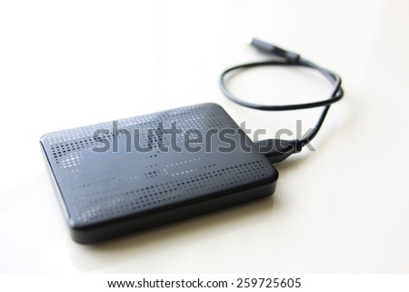 Portable external hard disk drive with USB cable on white background