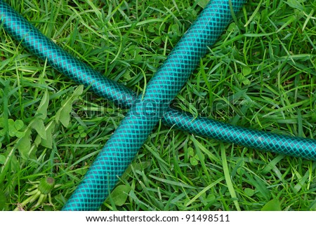 Portable garden plastic hosepipe on the green fresh grass field - stock photo