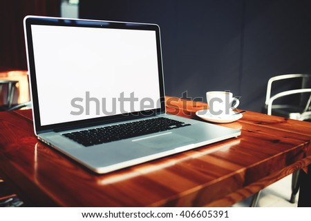 Portable laptop computer and cup of coffee lying on a wooden table in cafe bar interior, open net-book with copy space screen for your information content or text message, freelance work via internet  - stock photo