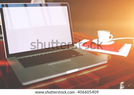 Portable laptop computer with copy space screen for your text message or advertising content, open net-book and cup of coffee lying with notepad on a wooden table in a contemporary interior  - stock photo