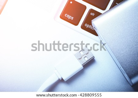 Portable power bank for charging mobile devices on laptop. - stock photo