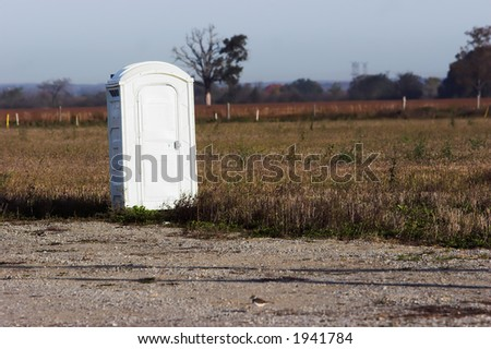Portable toilet in a field - stock photo