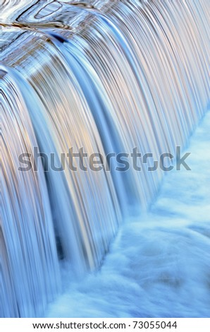 Portage Creek Cascade illuminated by reflected color from sunlit trees at sunrise and blue sky overhead, Michigan, USA - stock photo