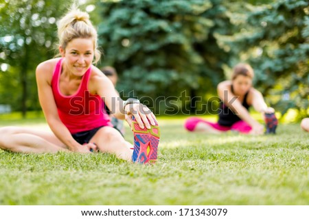Portait of a blond girl getting streching her legs before running outdoors - stock photo
