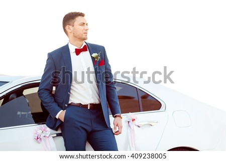 Portait of a young handsome man in suite near white widding decorated car.  Gorgeous guy, outdoors - stock photo