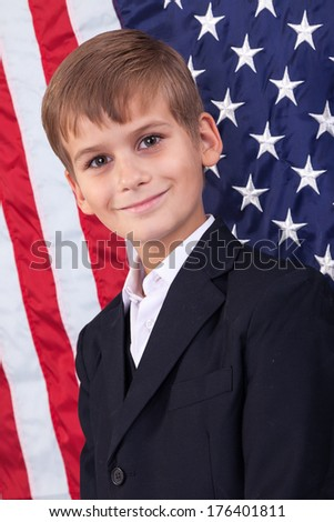 Portait of Caucasian boy  with American flag in background. - stock photo