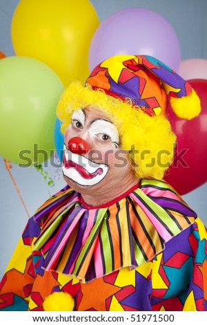 Portait of colorful clown making a sad face. - stock photo